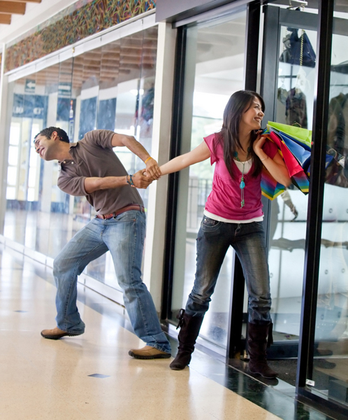 Man keeping a woman from entering a store and begging her to stop shopping