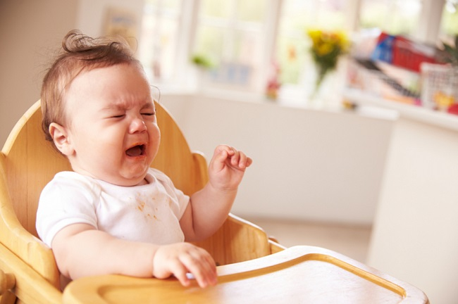 Unhappy Baby In High Chair At Meal Time