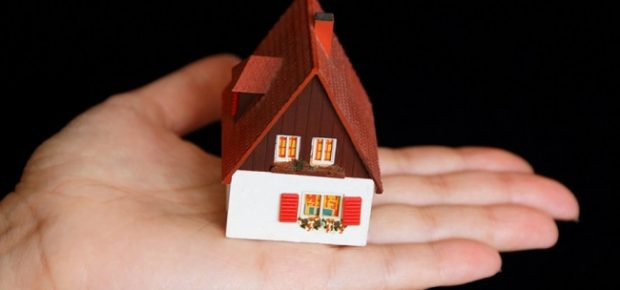 Image of dollhouse in human hand on black background