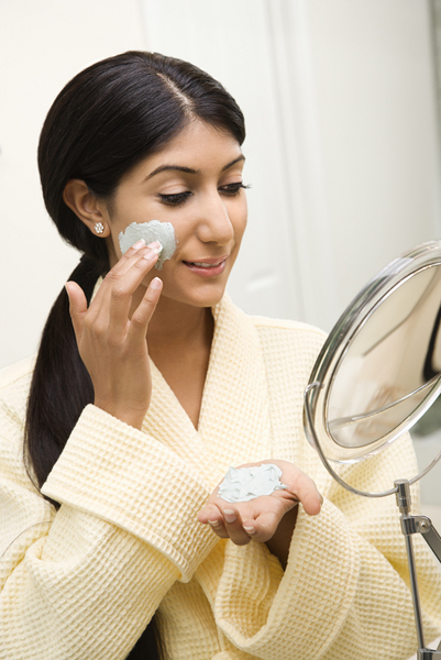 Smiling Asian/Indian young woman looking in mirror and applying facial scrub.